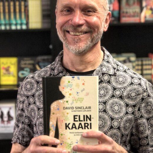 Kustantaja Niko Aula pitelee käsissään David Sinclairin Elinkaari-kirjaa.